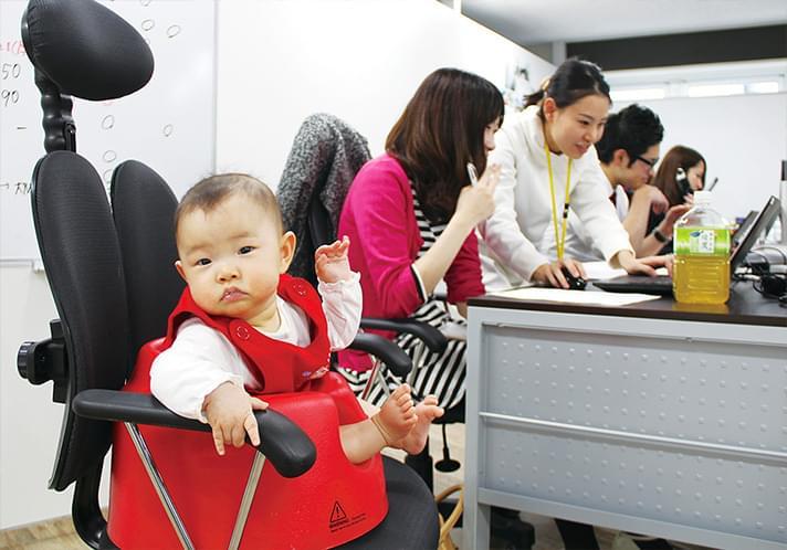 先輩社員による研修を受ける母親と、隣で座っている赤ちゃん