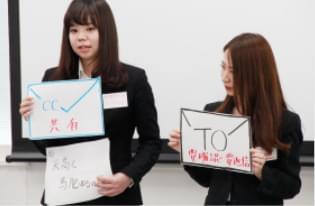 自作のポップを使ってビジネスマナーについて伝える2人の女性